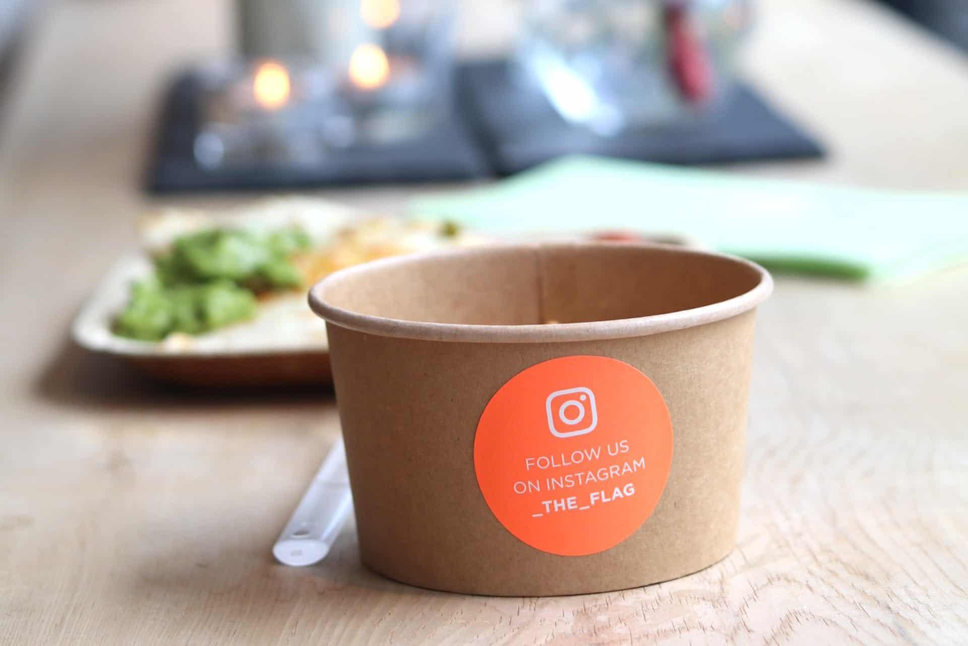 """Papierschüssel mit einem Aufkleber mit der Aufschrift """"Follow us on Instagram _THE_FLAG"""""""