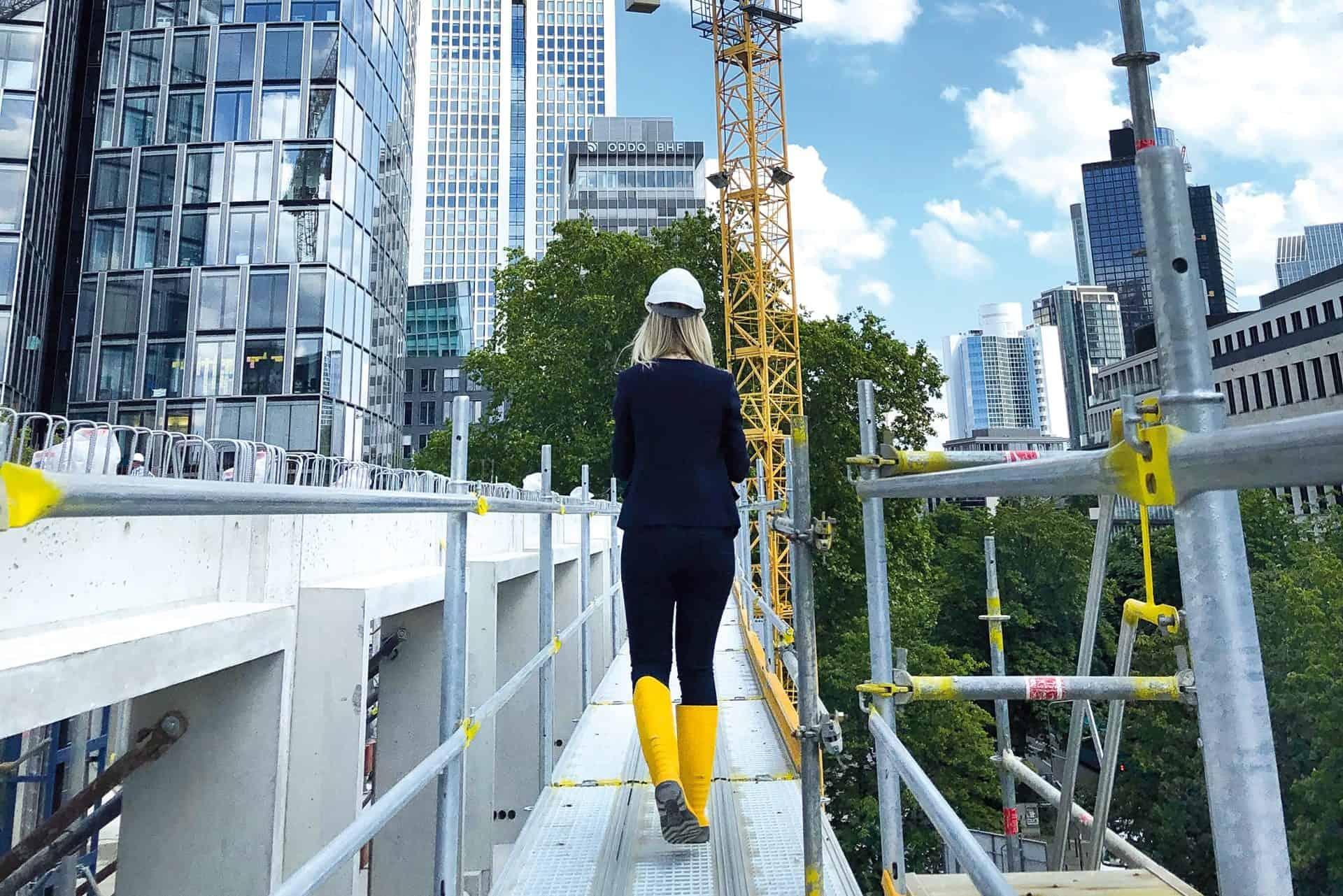 Eine Frau in gelben Gummistiefeln und weißem Sicherheitshelm läuft auf einem Baugerüst umgeben von den Dächern Frankfurts beim Bau des THE FLAG West M.