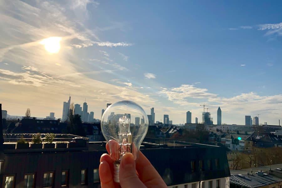 eine Hand hält eine transparente Glühbirne vor der Skyline von Frankfurt am Main