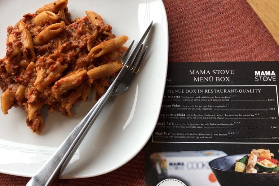 Mama Stove Speisekarte des THE FLAG Hotels neben einem Teller Penne Bolognese