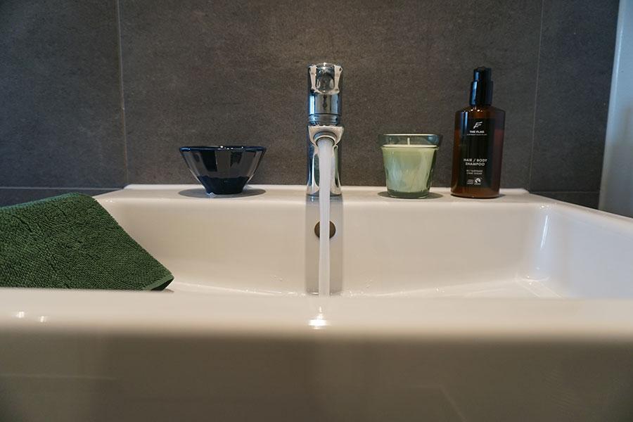 Nahaufnahme eines Waschbeckens mit laufendem Wasserhahn, Seifenspender, Kerze und Handtuch