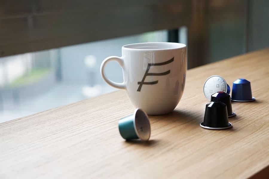 Eine weisse Tasse mit dem Logo von THE FLAG steht auf einem Holztisch vor dem Fenster. Daneben liegen dekorativ 5 Nespresso Kapseln.
