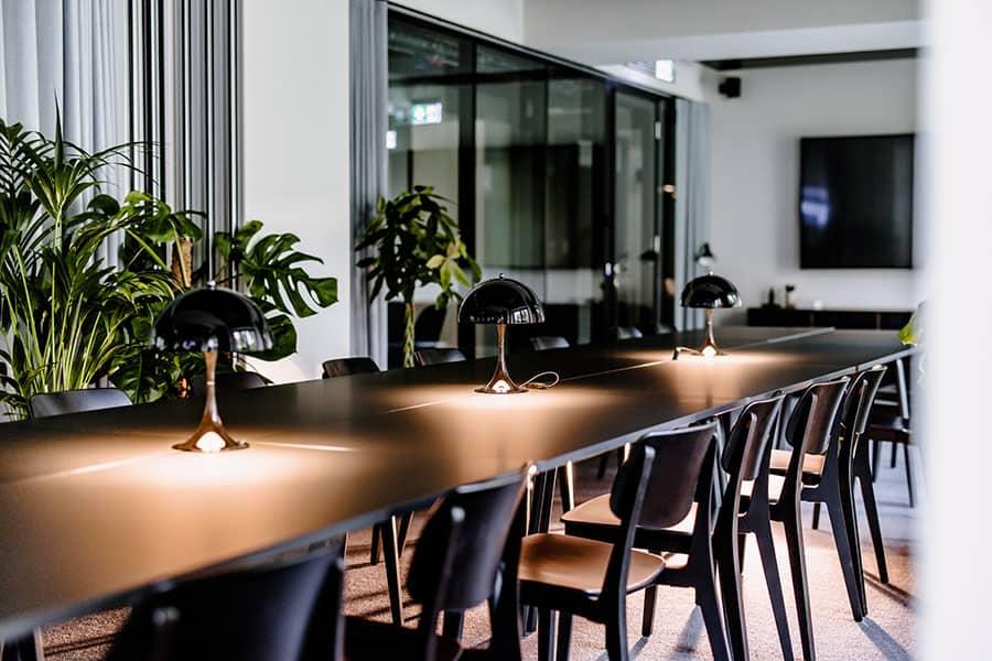 Ein Meeting-Raum im frankfurter Businesshotel mit breitem Konferenztisch, der mit mehreren Stühlen bestuhlt ist und vor einem modernen Monitor aufgebaut ist.