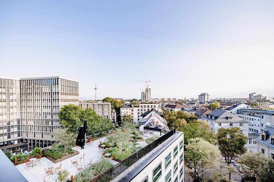 Außenaufnahme von oben mit Blick auf die möblierte Dachterrasse vom THE FLAG West M. und Aussicht auf die umliegenden Gebäude in Frankfurt.