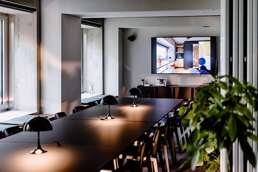 Besprechungsraum im Business-Hotel THE FLAG West M. in Frankfurt mit schwarzem Tisch und drei Pflanzen