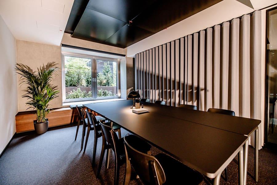 Besprechungsraum im Business-Hotel THE FLAG West M. in Frankfurt mit schwarzem Tisch und einer Pflanze